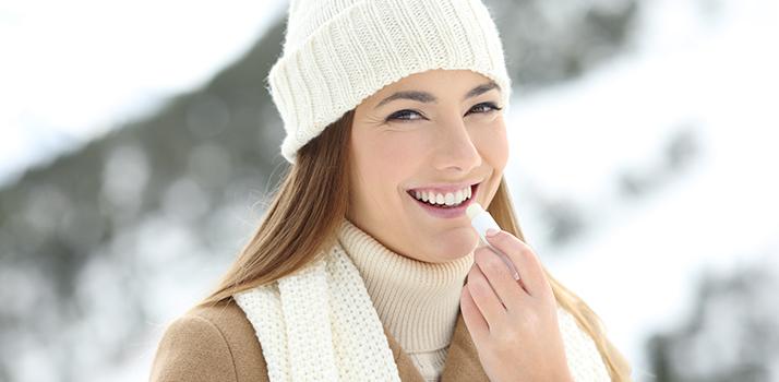 a woman putting on a lip balm